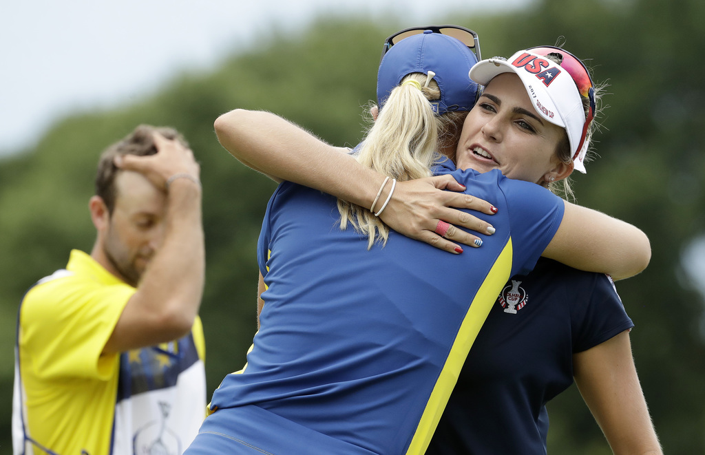 United States' Lexi Thompson, right, hugs Europe's Anna Nordqvist, of Sweden, after finishing on the 18th hole during their singles match in the Solhe...