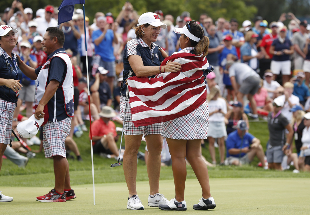United States' Lizette Salas celebrates with United States captain Juli Inkster, left, after her singles match in the Solheim Cup golf tournament, Sun...