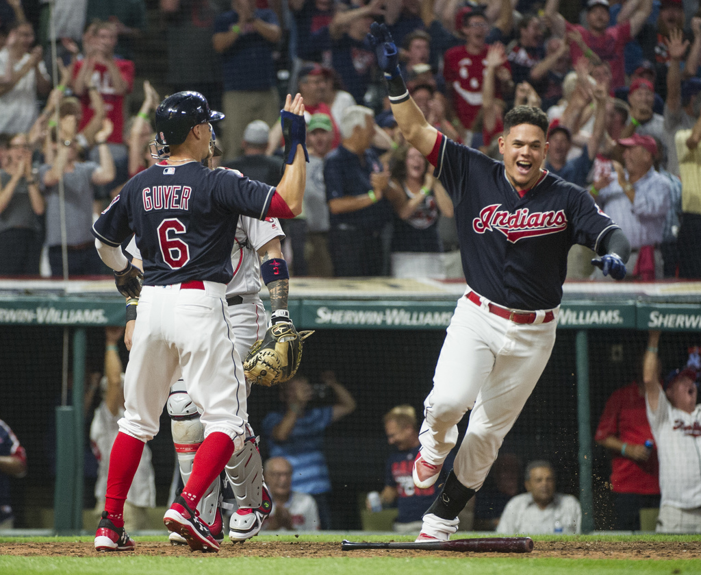 Cleveland Indians' Brandon Guyer (6) is congratulated by teammate Giovanny Urshela after scoring the winning run against the Boston Red Sox in the nin...