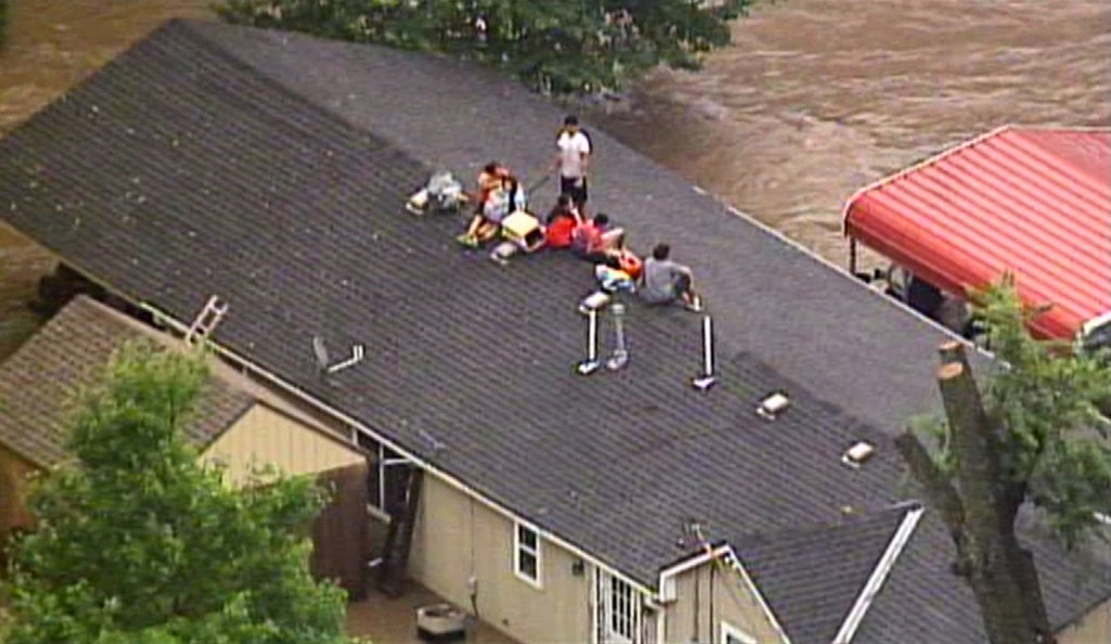 This aerial photo from a video by KCTV5 shows a family forced onto the roof of a home in Overland Park, Kan., on Tuesday, Aug. 22, 2017, after heavy r...