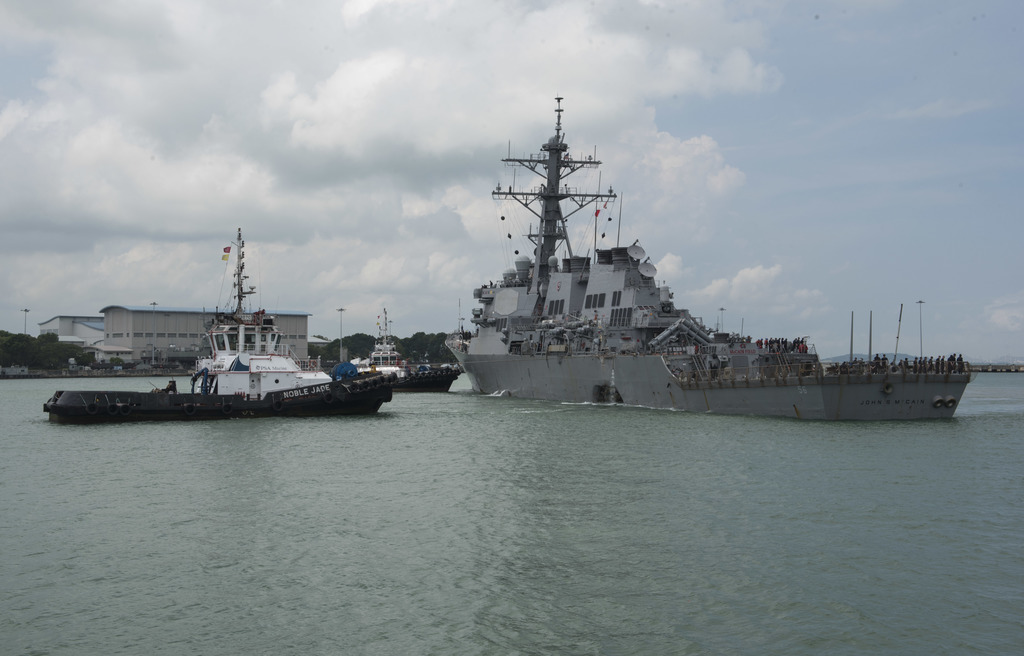 In this Aug. 21, 2017, photo provided by U.S. Navy, tugboats from Singapore assist the Guided-missile destroyer USS John S. McCain (DDG 56) as it stee...
