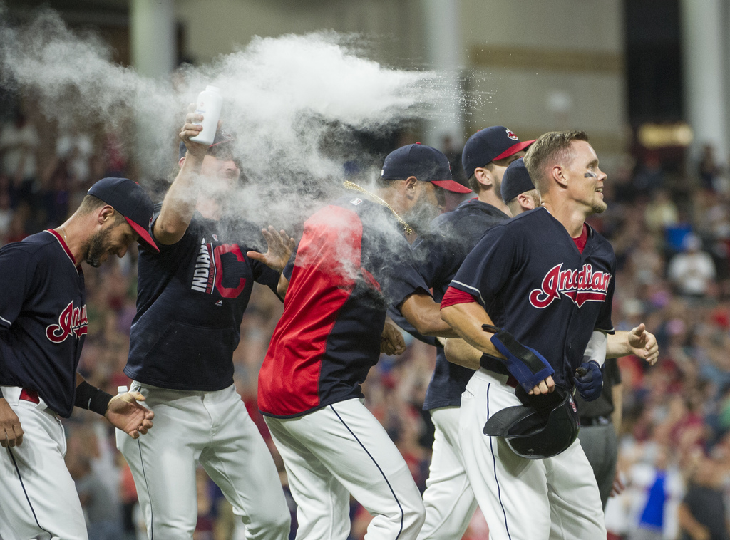 Cleveland Indians' Brandon Guyer, right, is mobbed by his teammates after scoring the winning run in the bottom of the ninth inning of a baseball game...