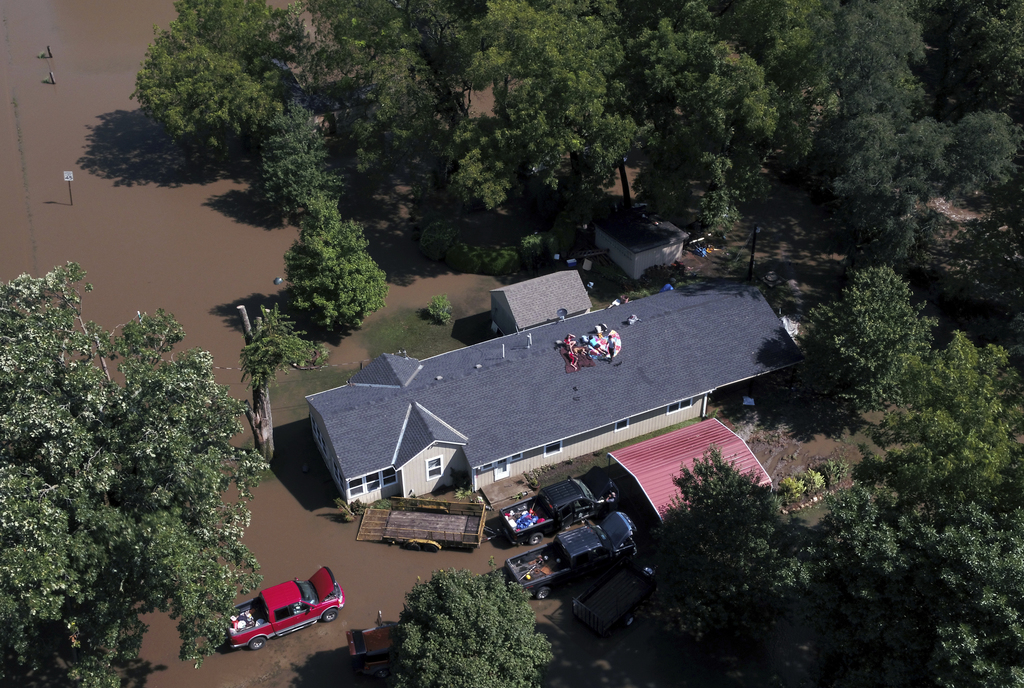 Overland Park Fire Department officials wait for floodwaters to recede before attempting to rescue a family  stranded on the roof of their home in  Ov...