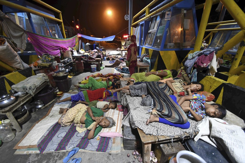 FILE- In this Aug. 19, 2017 file photo, flood affected people sleep by the national highway toll plaza at Araria district, in the eastern Indian state...