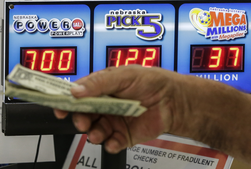 A customer hands over money for a Powerball ticket in Omaha, Neb., Wednesday, Aug. 23, 2017. Lottery officials said the grand prize for Wednesday nigh...