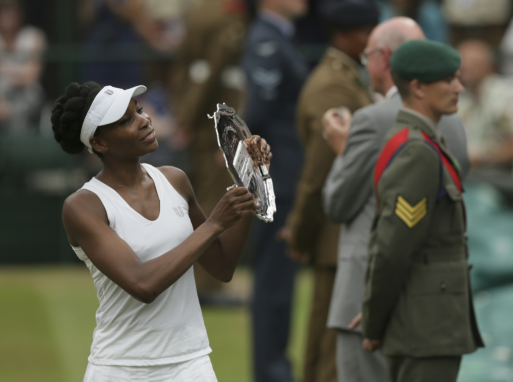 File-This July 15, 2017, file photo shows Venus Williams of the United States holding the runners-up plate after losing to Spain's Garbine Muguruza in...