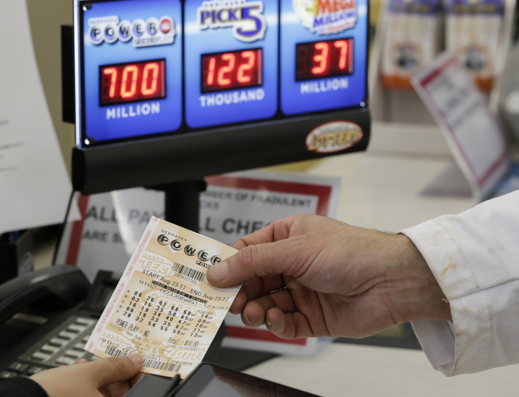 A customer is handed a Powerball ticket in Omaha, Neb., Wednesday, Aug. 23, 2017. Lottery officials said the grand prize for Wednesday night's drawing...