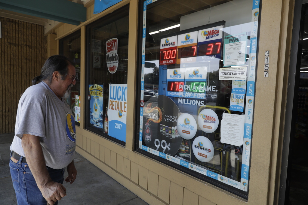 Mike Brum looks at a display advertising lottery tickets for sale Wednesday, Aug. 23, 2017, in Fremont, Calif. Officials estimated jackpot for Wednesd...