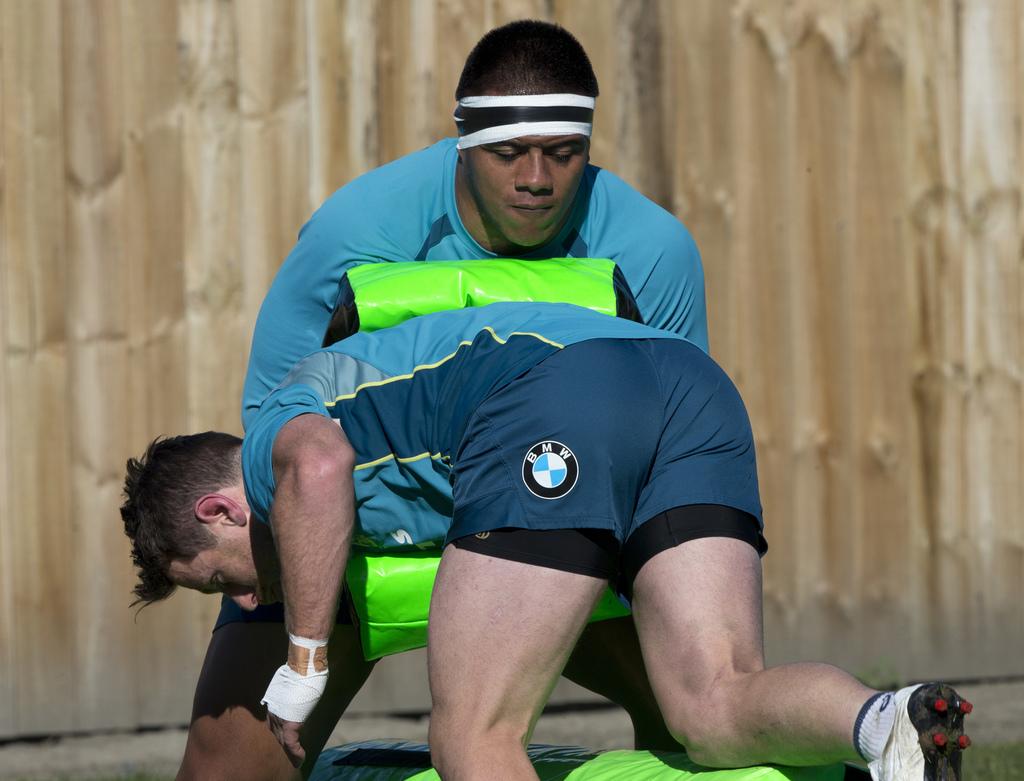 Australian prop Allan Alaalatoa holds a tackle bag as teammate Bernard Foley runs into him during a training session in Christchurch, New Zealand, Thu...