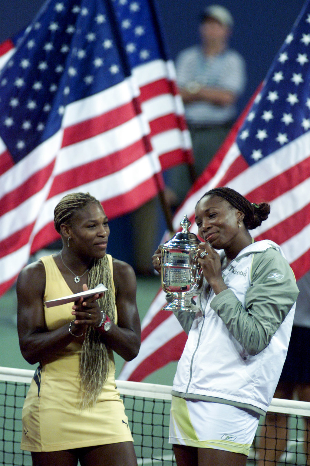 File-This Sept. 8, 2001, file photo shows Venus Williams admiring her trophy as sister Serena, left, looks on after Venus won the final of the US Open...
