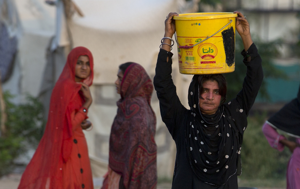 In this Tuesday, Aug. 22, 2017 photo, a woman carries water for her family at a tube well in Rawalpindi, Pakistan. A new study suggests some 50 millio...