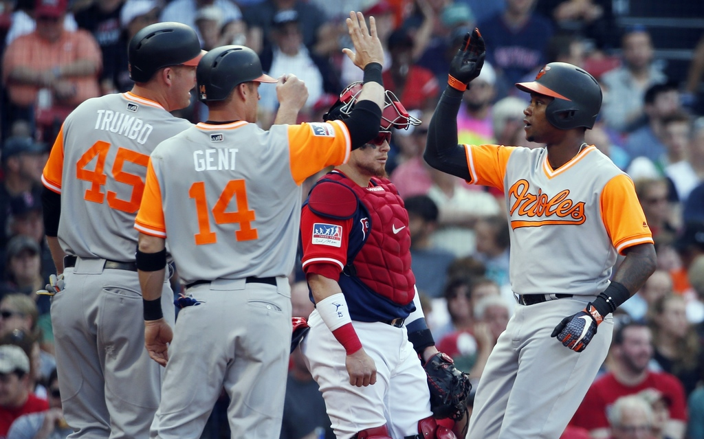Baltimore Orioles' Tim Beckham, right, celebrates his three-run home run in front of Boston Red Sox's Christian Vazquez that also scored Mark Trumbo (...