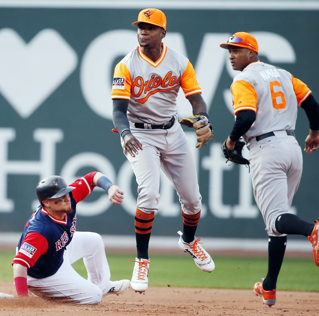 Boston Red Sox's Christian Vazquez, left, is forced out at second base as Baltimore Orioles' Tim Beckham, center, turns the double play on Eduardo Nun...