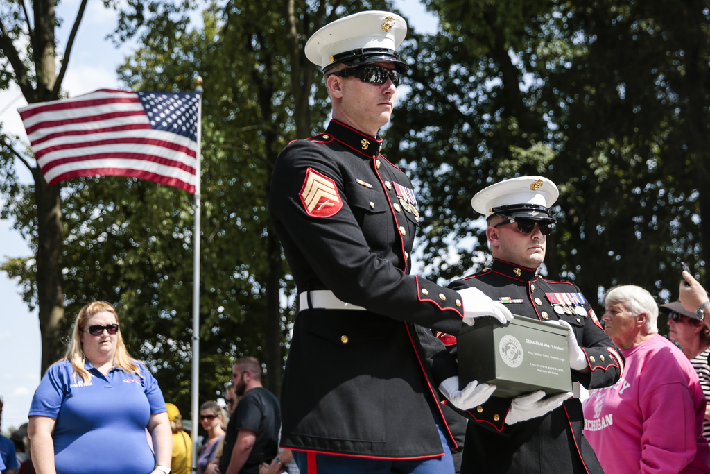 Jon North, center, and Jeffrey DeYoung, right, carry the urn containing the remains of Cena the 10-year-old black lab, during the memorial service at ...