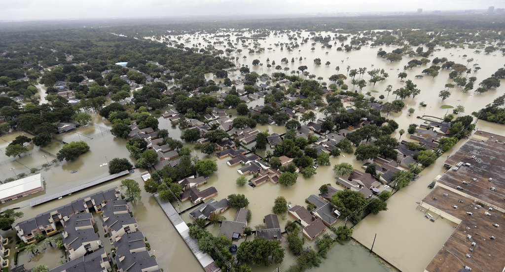 FILE - In this Aug. 29, 2017 aerial file photo, a neighborhood near Addicks Reservoir are flooded by rain from Harvey, in Houston. Houston's populatio...