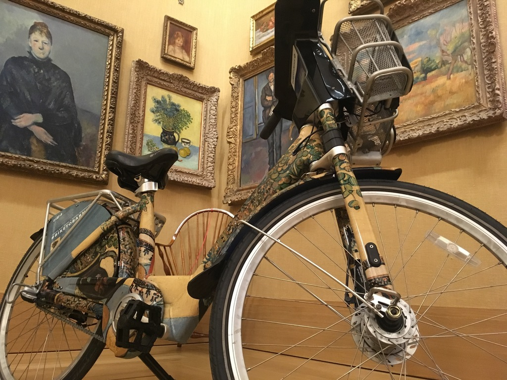 """An Indego bicycle outfitted with an image of Vincent van Gogh's 1888 painting """"Still Life"""" is posed in front of the original painting at The Barnes Fo..."""
