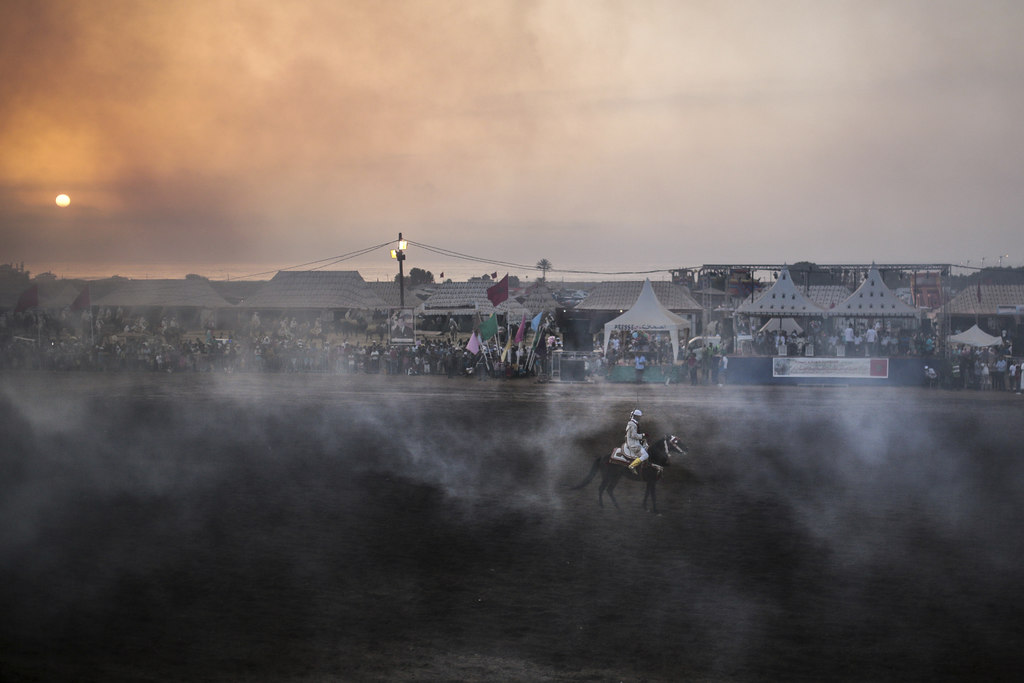 In this Thursday, Aug. 17, 2017 photo, a horseman is surrounded by gunpowder smoke after a successful charge while taking part in Tabourida, a traditi...