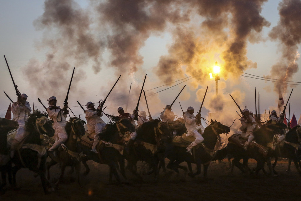 In this Thursday, Aug. 17, 2017 photo, horse riders fire their gunpowder filled rifles as they take part in Tabourida, a traditional horsemanship show...