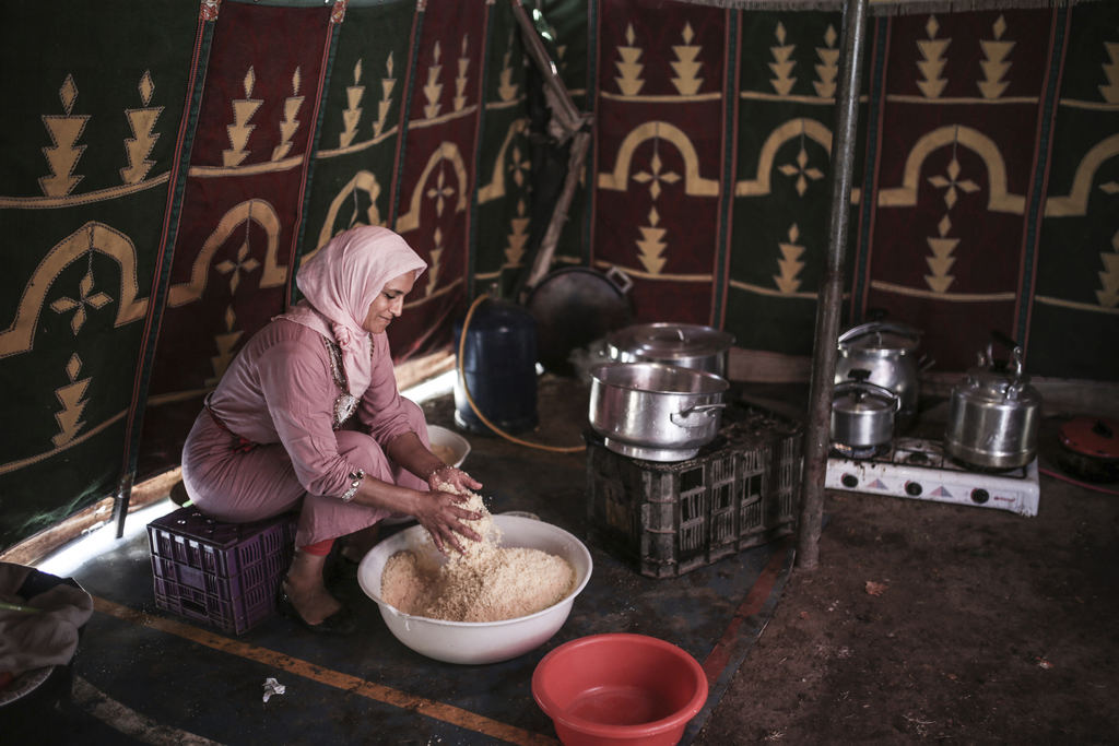 In this Thursday, Aug. 17, 2017 photo, a woman cooks couscous for horsemen taking part in Tabourida, a traditional horse riding show also known as Fan...