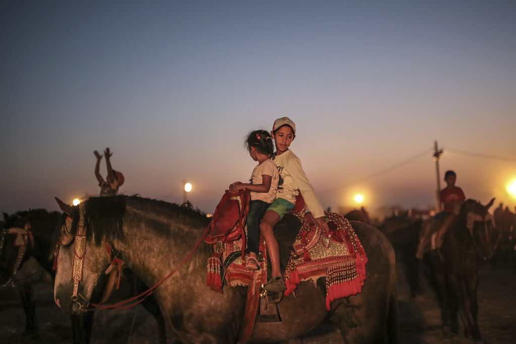 In this Thursday, Aug. 17, 2017 photo, children play on horses, after the end of Tabourida, a traditional horse riding show also known as Fantasia, in...
