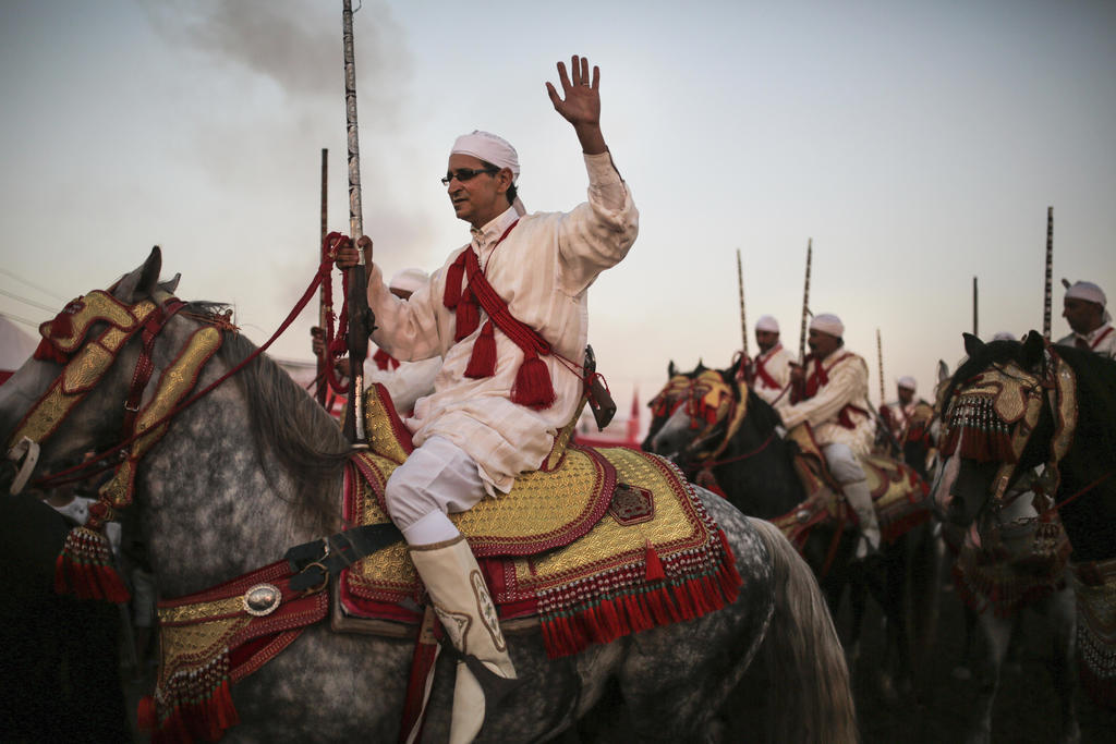 In this Thursday, Aug. 17, 2017 photo, a horseman waves to the crowd after a successful charge during Tabourida, a traditional horse riding show also ...