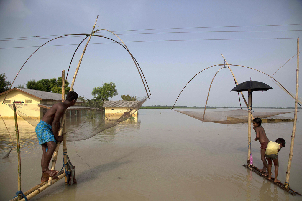 In this Tuesday, Aug. 15, 2017, file photo, villagers fish in floodwaters in Morigaon district, east of Gauhati, northeastern state of Assam. This wee...