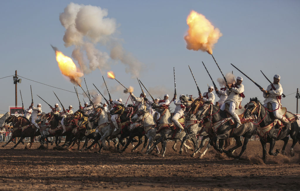 In this Thursday, Aug. 17, 2017 photo, a troupe charges and fires their rifles during Tabourida, a traditional horse riding show also known as Fantasi...