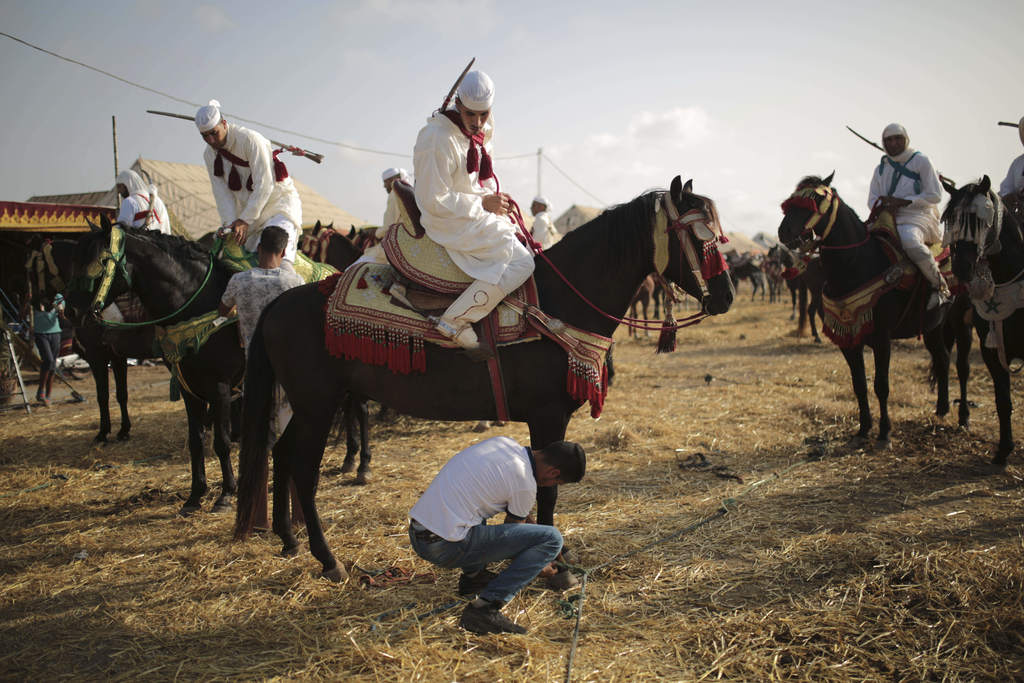 In this Thursday, Aug. 17, 2017 photo, horsemen prepare their horses before taking part in Tabourida, a traditional horse riding show also known as Fa...