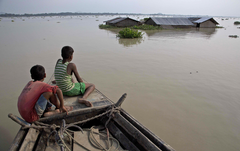 In this Aug. 15, 2017, file photo, flood affected villagers travel by boat in floodwaters in Morigaon district, east of Gauhati, northeastern state of...