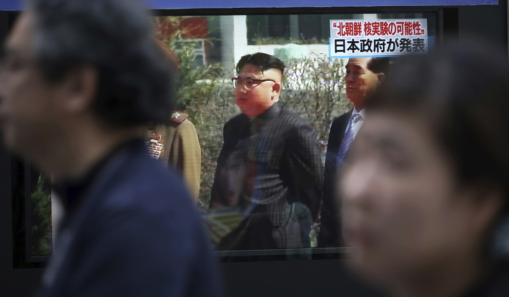 People walk past a TV news program on a public screen showing an image of North Korean leader Kim Jong Un while reporting North Korea's a possible nuc...