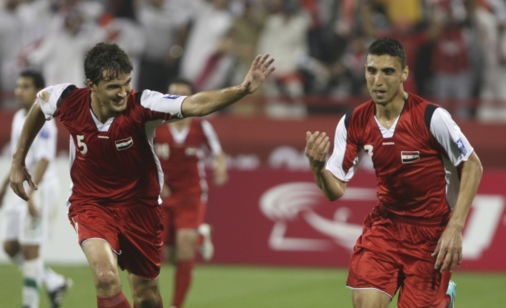 FILE - In this Jan. 9, 2011 file photo, Syria's midfielder Abulrazaq al-Hussein, left, celebrates with teammates after scoring his team's second goal ...