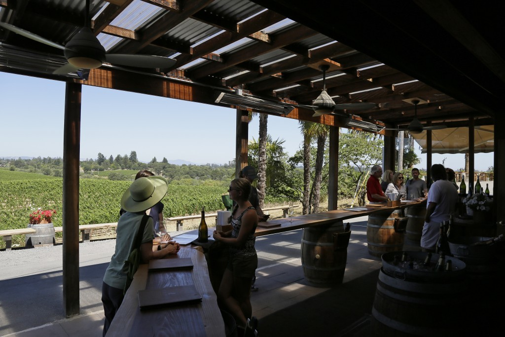 In this photo taken Monday, July 10, 2017, people visit the tasting room at Iron Horse Vineyards in Sebastopol, Calif. Set on a hilltop in Sonoma's Gr...