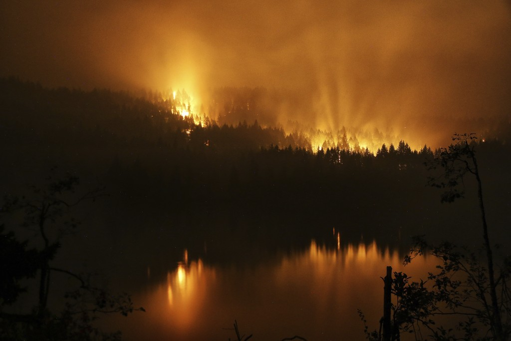 A wildfire continues to burn on the Oregon side of the Columbia River Gorge near Cascade Locks, Ore., and the Bridge of the Gods, late Tuesday, Sept. ...