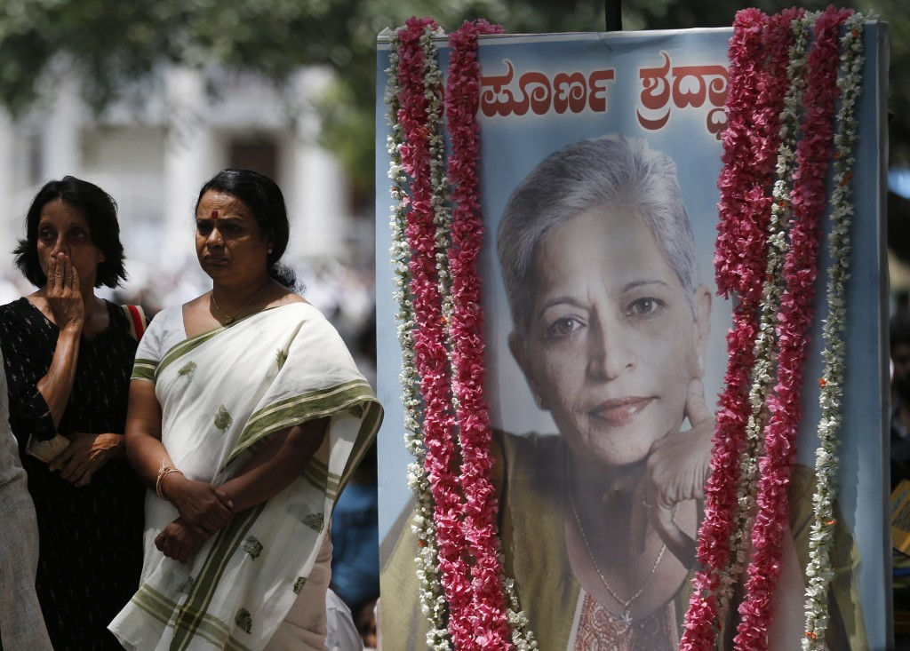 Mourners stand next to a portrait of Indian journalist Gauri Lankesh during the public viewing of her body in Bangalore, India, Wednesday, Sept. 6, 20...