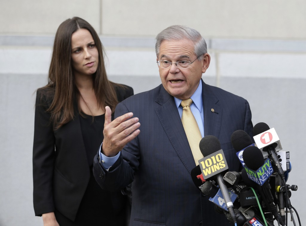 While his daughter Alicia Menendez looks on, Sen. Bob Menendez talk to reporters as he arrives to court for his federal corruption trial in Newark, N....