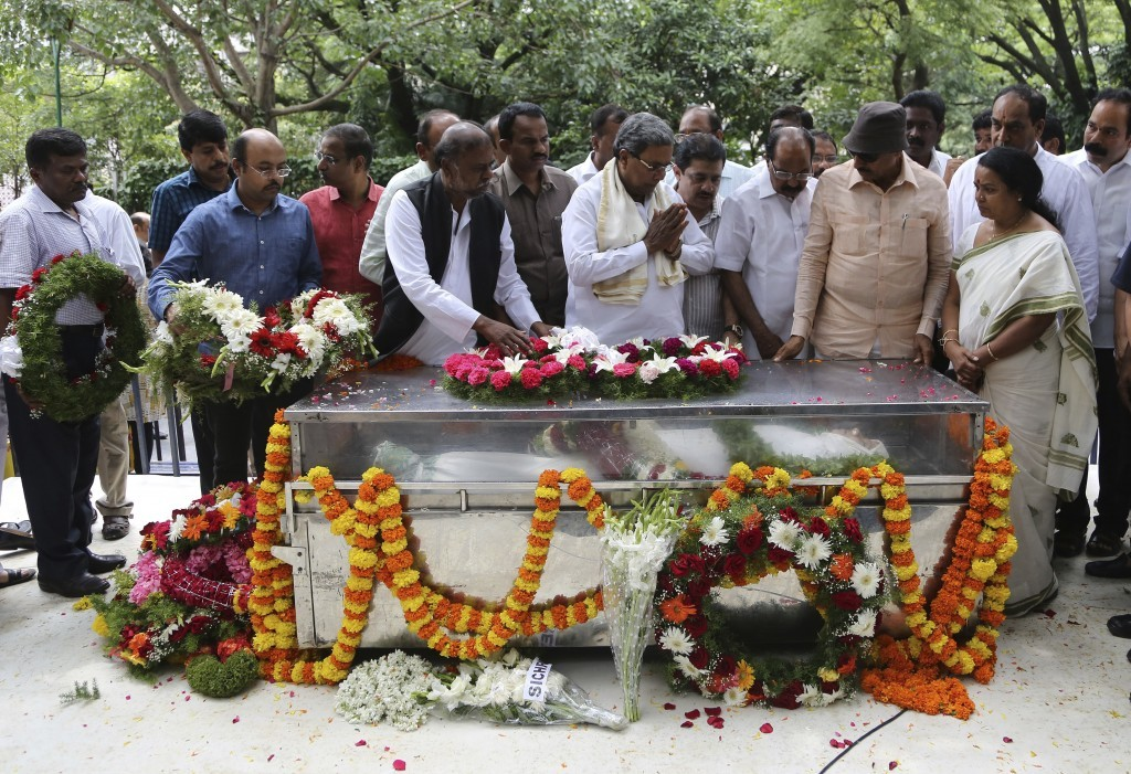 India's Karnataka state Chief Minister Siddaramaiah, center, pays his respects next to the casket of Indian journalist Gauri Lankesh during the public...