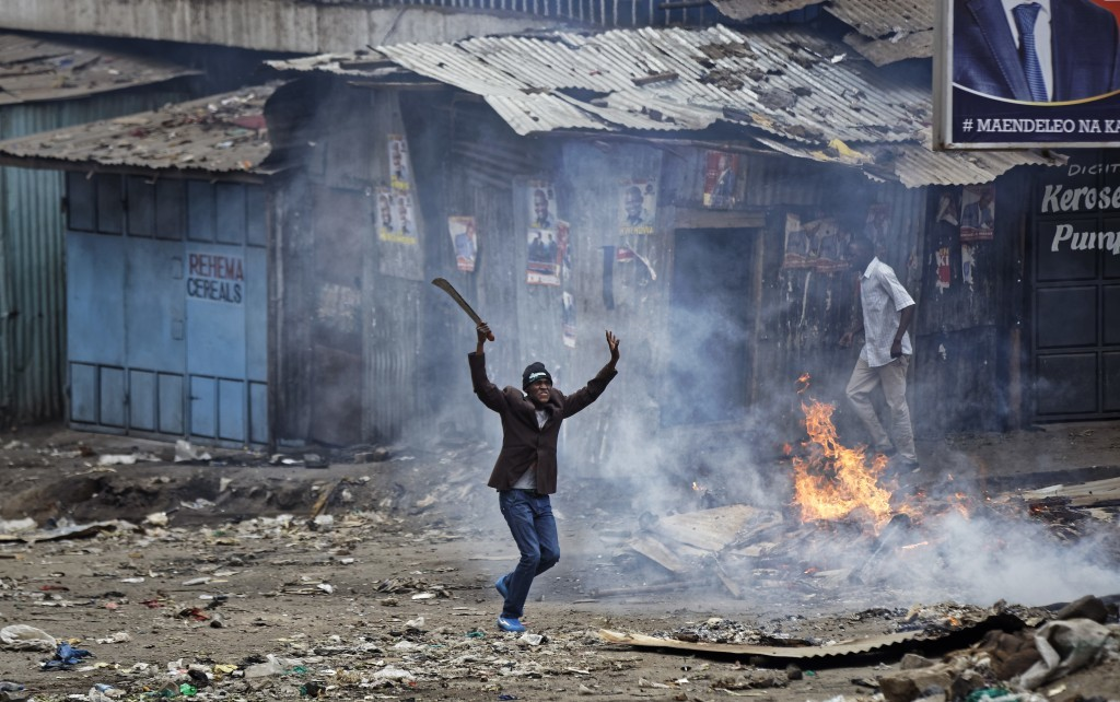 """FILE - In this Saturday, Aug. 12, 2017 file photo, a man brandishing a """"panga"""" machete challenges police near a burning barricade during clashes betwe..."""
