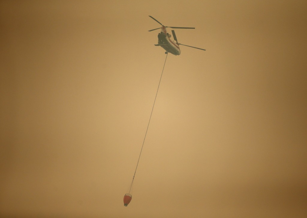 A helicopter with a water bucket flies through dense smoke near Stevenson, Wash., Wednesday, Sept. 6, 2017, as it works to battle the Eagle Creek wild...