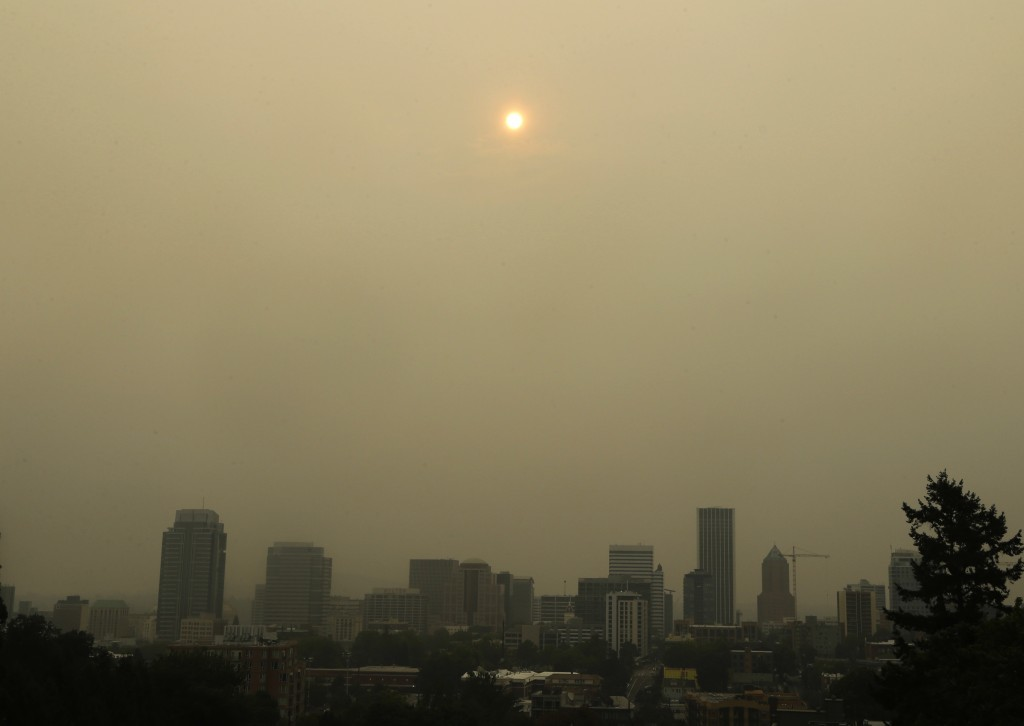 The sun is barely visible over downtown Portland, Ore., Wednesday, Sept. 6, 2017, as seen through smoke from wildfires burning in the Columbia River G...