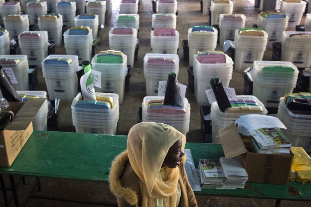FILE - In this Monday, Aug. 7, 2017 file photo, a Kenyan election volunteer walks past ballot boxes and electoral material to be distributed to variou...