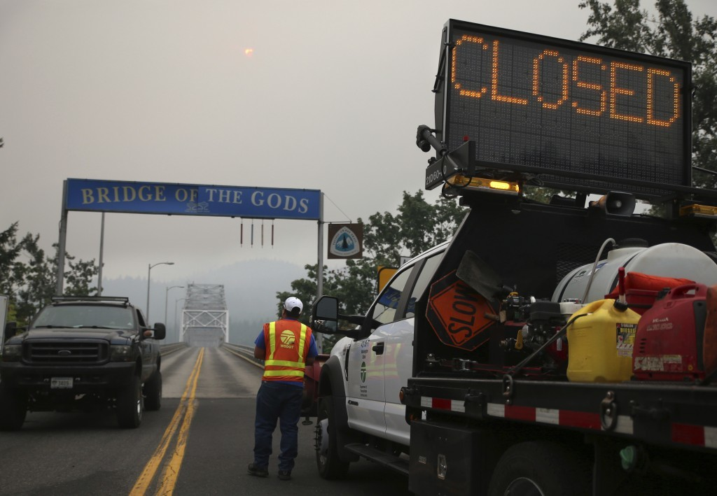 A barricade closes the Bridge of the Gods, spanning the Columbia River between Washington and Oregon states, near Stevenson, Wash., Wednesday, Sept. 6...