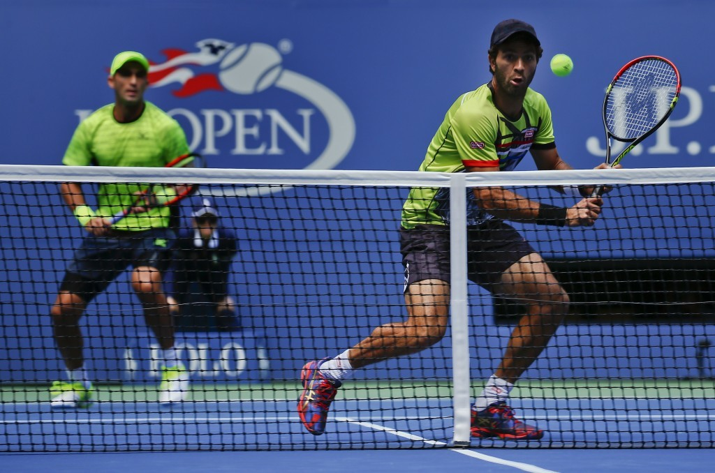 Jean-Julien Rojer, of Holland, right, returns a shot as doubles partner Horia Tecau, of Romania, looks on during the championship doubles match of the...