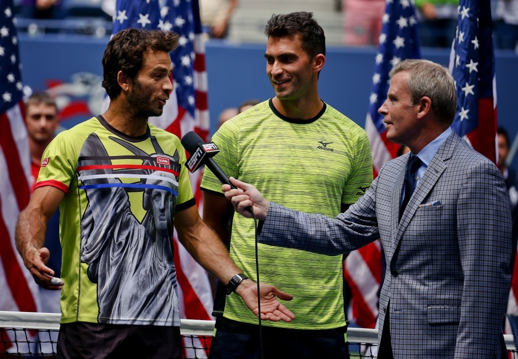 Dutch tennis player Jean-Julien Rojer, left, talks with ESPN reporter Tom Rinaldi as doubles partner Horia Tech, of Romania, listens, after the two wo...