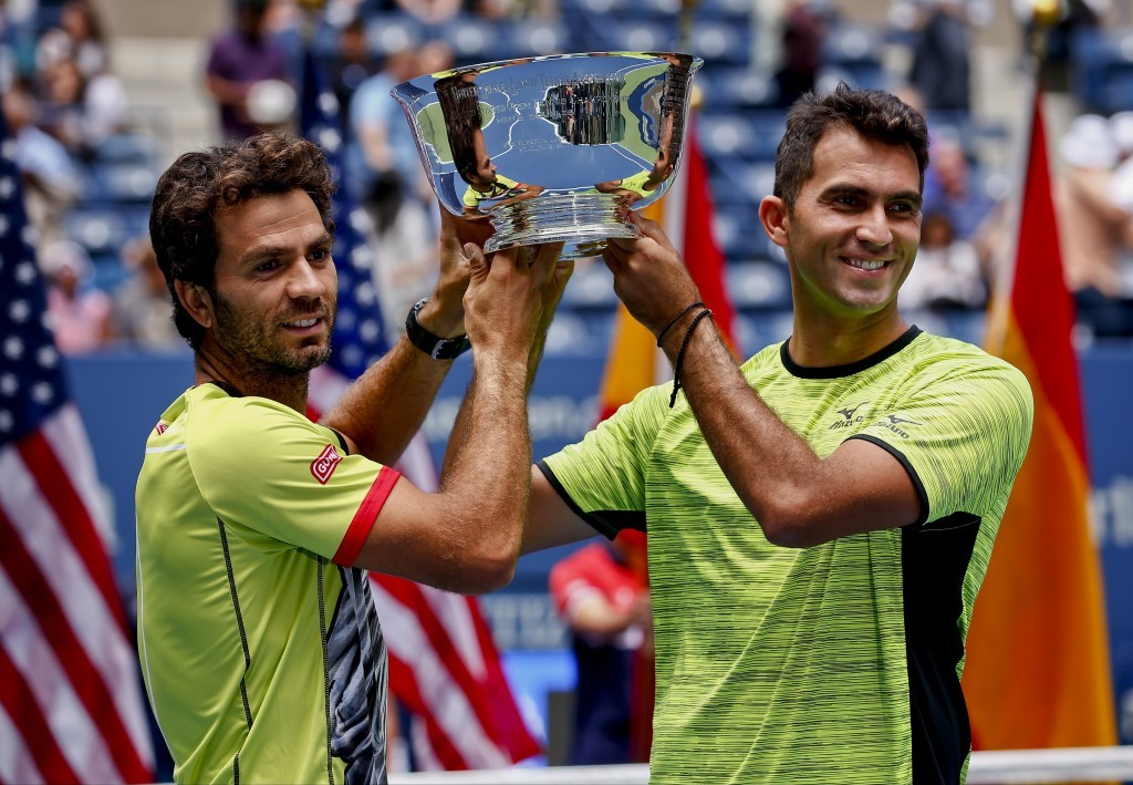Jean-Julien Rojer, of Holland, left, and Horia Tecau, of Romania, hold up the championship trophy after beating Marc Lopez and Feliciano Lopez, both o...