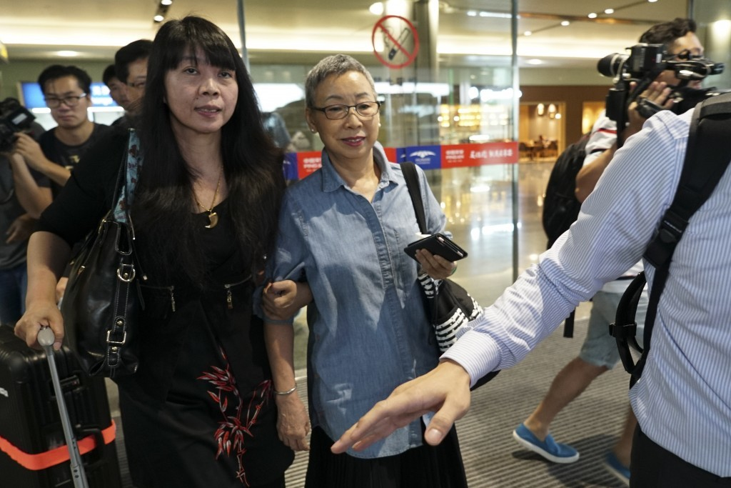 Kou Shou-chin, mother of detained Taiwanese activist Lee Ming-che, center, is chased by reporters as she arrives at the Changsha International Airport