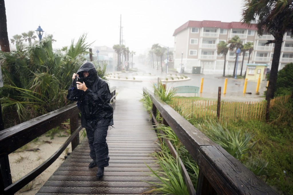 Bethany Kellam walks onto the southend beach of Tybee Island, Ga., Monday, Sept., 11, 2017. The National Weather Service placed most of Georgia under ...
