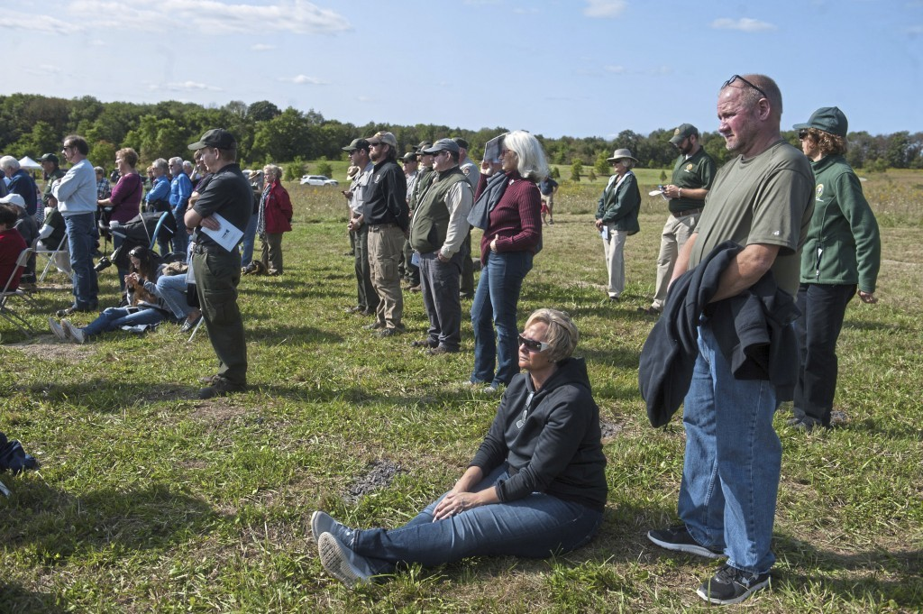"""Patti Show, 50, of Farmington, sits at the feet of her husband Doug, right, 51, as they listen during the """"sound breaking"""" ceremony at the future site..."""