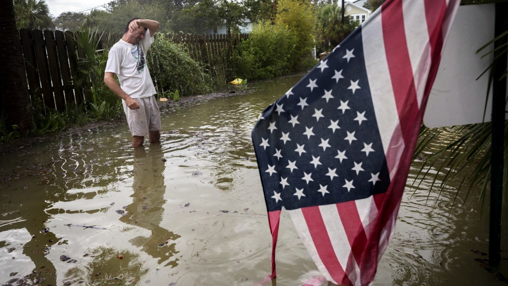Tybee Island resident Joe Murphy wipes the sweat off his face while standing in knee deep water from Tropical Storm Irma outside his house, Monday, Se...