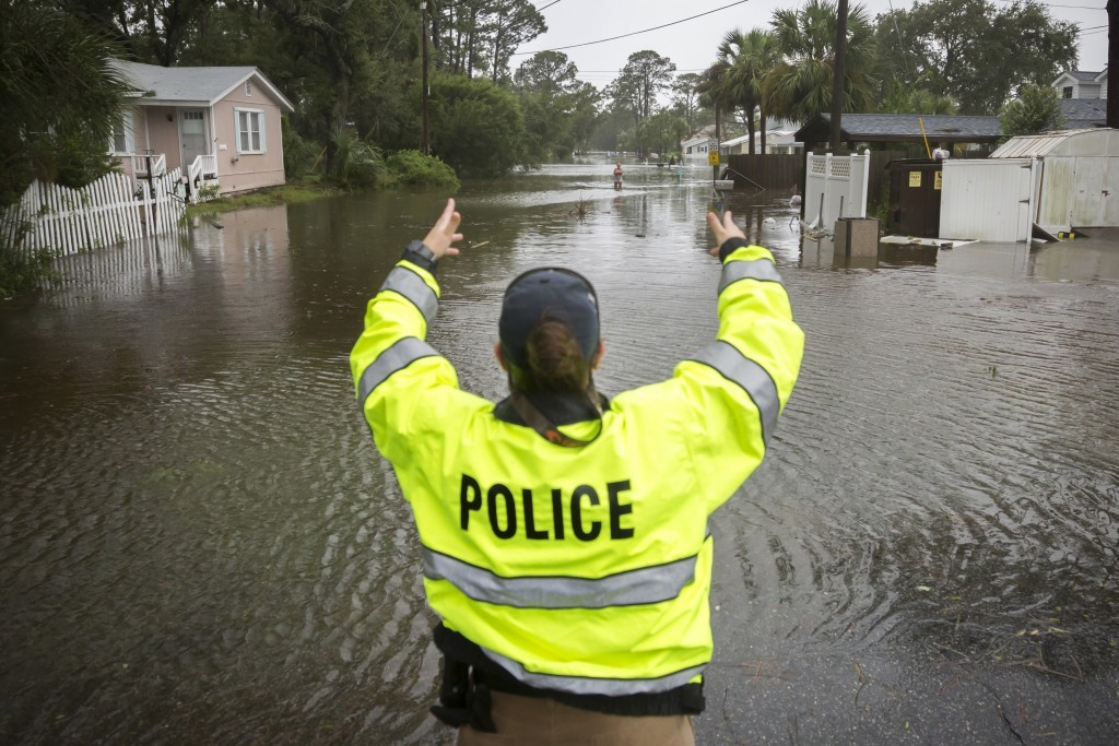 A City of Tybee police officer checks the well being of a resident fleeing her flooded home on Tybee Island, Ga., Monday, Sept., 11, 2017. Parts of th...