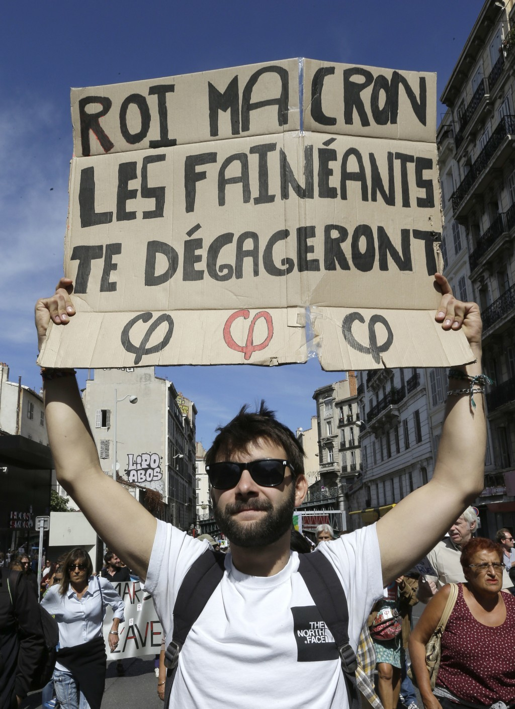 """A demonstrator holds a placard reading"""" King Macron, idlers will clear you"""", during a nationwide day of protest against government labor law, in Marse..."""